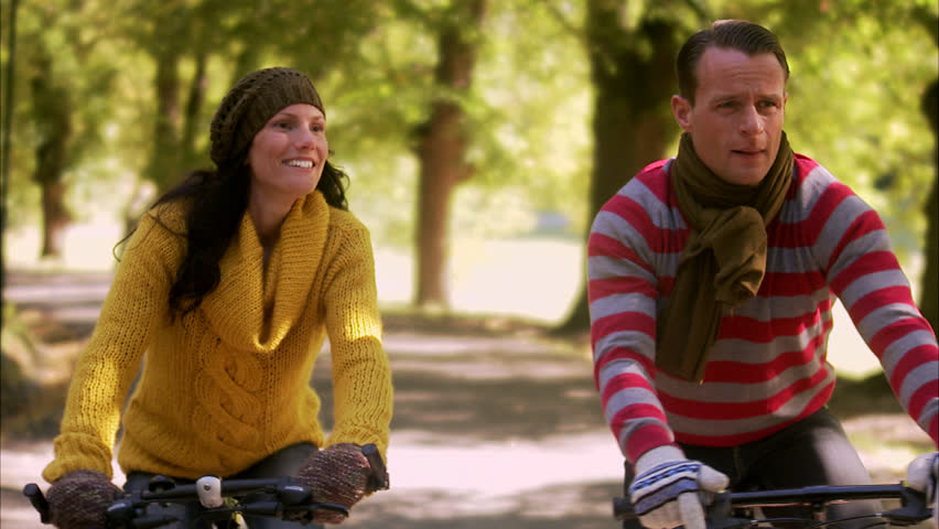 A woman and a man riding bicycles an autumn day