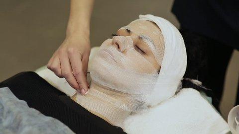 A bandage mask using gauze fabric. Application of cream on the laid gauze cloth on the face.