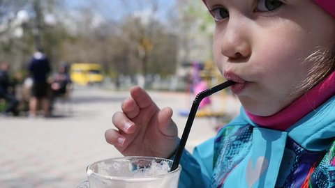Little child girl sucks a cacao drink with a plastic straw closeup face