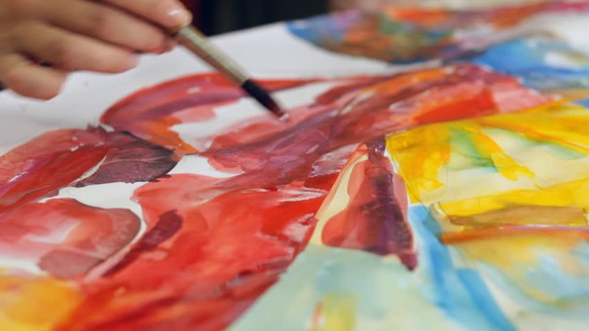 Woman artist painting watercolor paints
