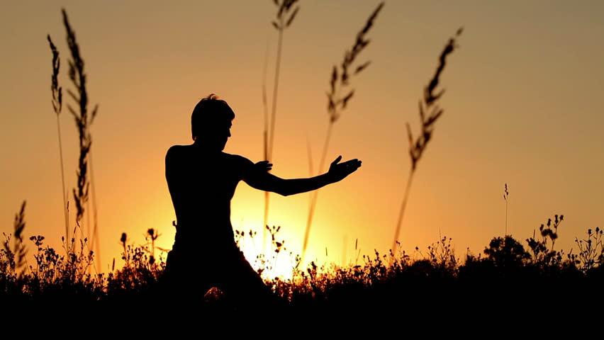 Young man training martial arts at sunset