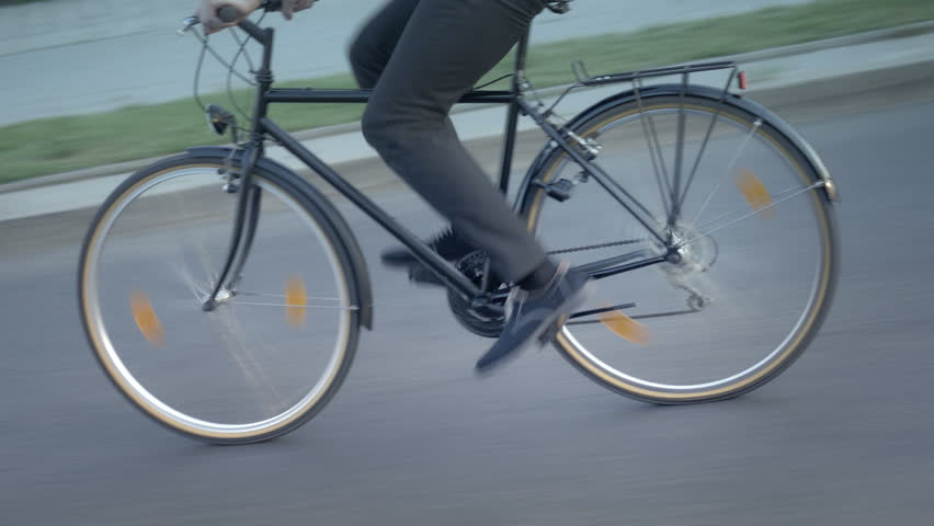 Close-up of man riding a bike to work on the street. Office worker choosing eco-friendly transport for his commute.