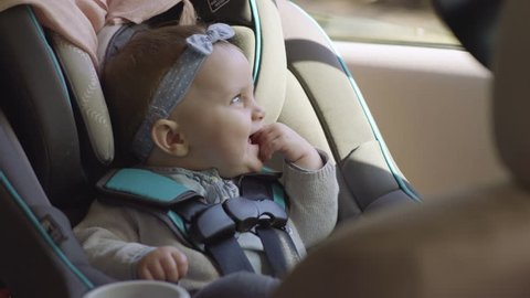 Adorable Smiley Baby Girl Sits In Her Car Seat, She Looks Out Window, And Around Car