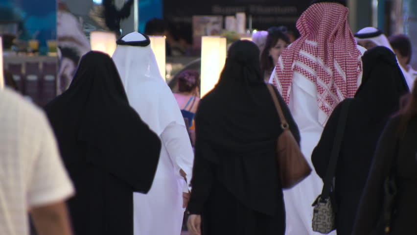 DUBAI, UAE - CIRCA FEBRUARY 2016: A busy modern mall in Arabia despite the effects of the low oil price on the economy, showing a large Emirati family wearing traditional Arab dress.