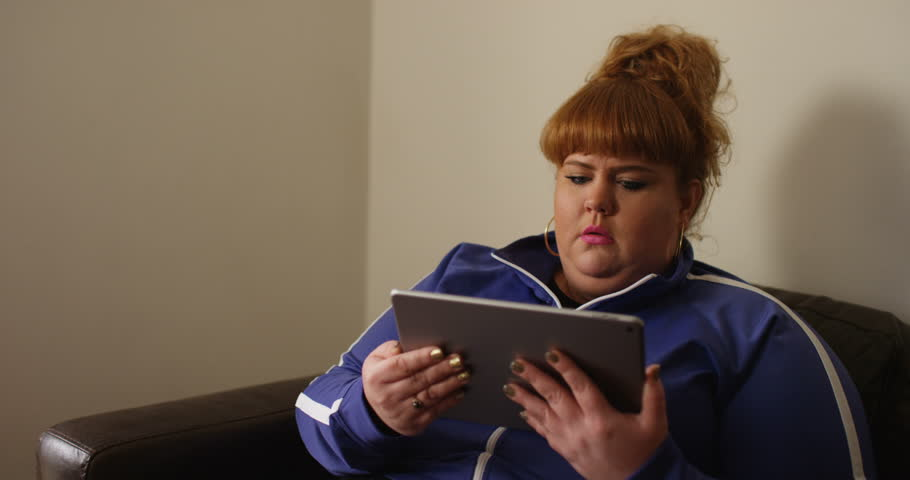 4K Funny overweight woman reacting with shock, watching a film on computer tablet
