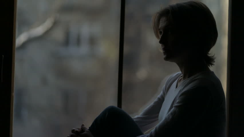 Depressed woman sitting on the sill and looking out the window, broken-hearted