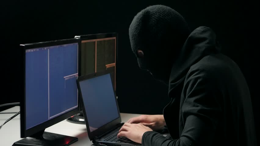 Hacker in balaclava cracking code using laptop and computers from his dark hacker room | Shutterstock HD Video #26232839