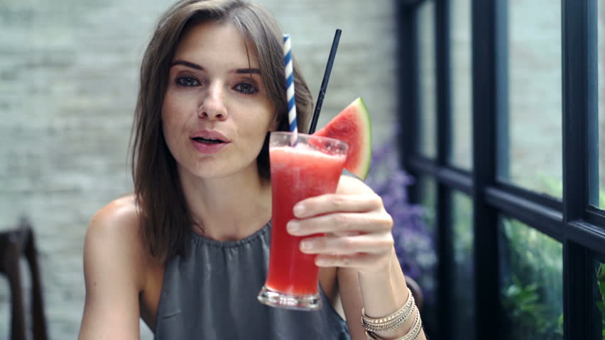 Beautiful woman raising toast to camera and drinking juice in cafe, 4K