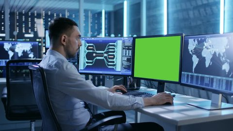 Technical Controller/ Operator Working at His Workstation with Multiple Displays (Green Screen Mock-up). Possible Power Plant/ Airport Dispatcher/ Dam Worker/ Government Surveillance/ Space Program.