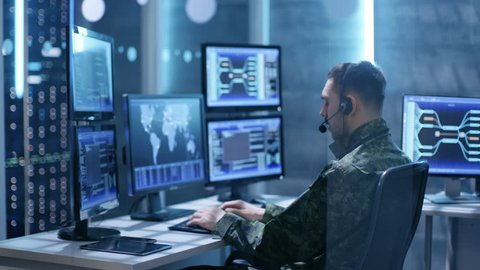 Female and Male Military Technical Support Professional Giving Instructions into Headsets. They're in System Control Room with Many Working Screens.