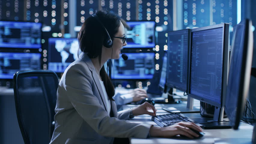In the System Control Center Technical Support Team Gives Instructions with the Help of the Headsets. Possible Air Traffic/ Power Plant/ Security Room Theme. Shot on RED EPIC-W 8K Helium Cinema Camera | Shutterstock HD Video #26262242