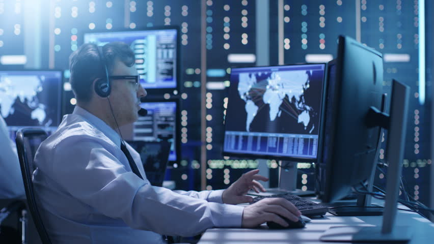 Professional Technical Support Personnel Working in a System Control Center. We See Many Working Displays with Various Data Visible on Them. Shot on RED EPIC-W 8K Helium Cinema Camera.   Shutterstock HD Video #26262905