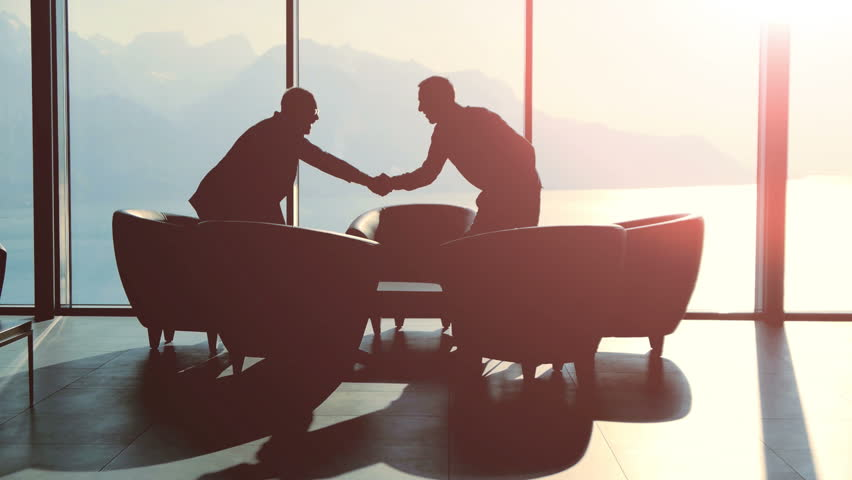 silhouette of two business people talking together sitting in modern lobby hall at sunset light. financial sales corporate concept background