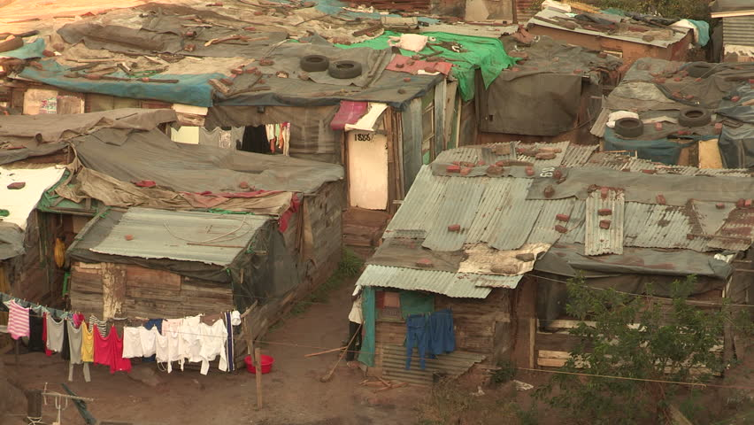 Informal settlements close together in Durban, people going  in and out of their shacks.