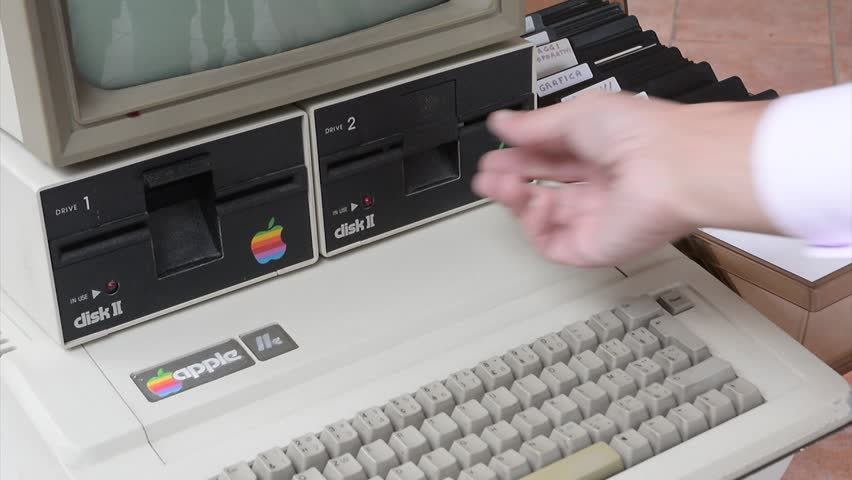 Aged Apple computer and hand insert floppy inside