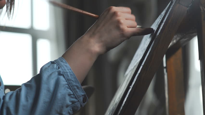The artist paints a woman on canvas and smears a broad brush. Canvas stands on the easel. The artist draws at the easel. The drawing process: a close-up of the brush and canvas
