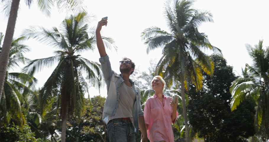 Couple Walk Using Cell Smart Phone Under Palm Trees, Man Hold Hand Up Video Call, Smiling Man And Woman Online Communication Slow Motion 60 | Shutterstock HD Video #26303225