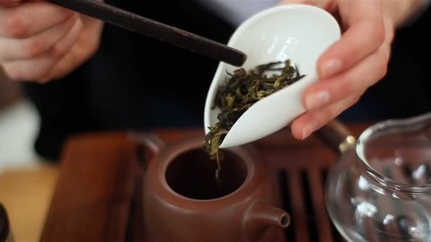 Adding dry tea leaves into teapot using special spoon during traditional Chinese tea ceremony Gongfu. Female hand slowly filling small pot with oolong green tea carefully pouring it from cha he holder