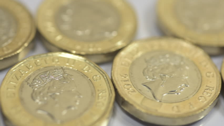 New British one pound coins sterling close up HD footage against white background with a sliding camera move