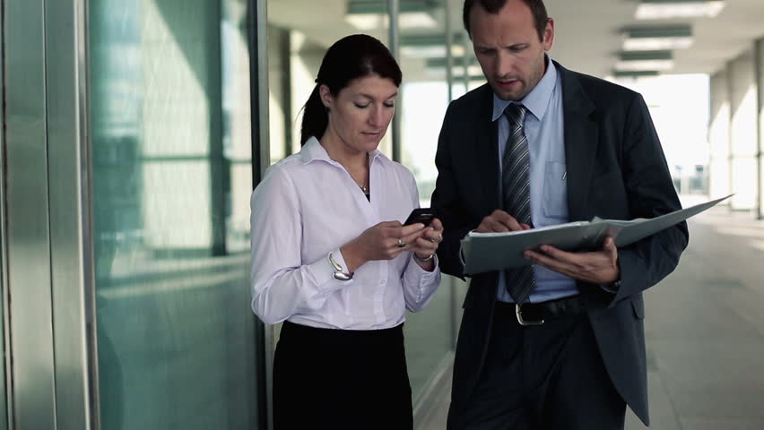 Business people with smartphone and documents in the city