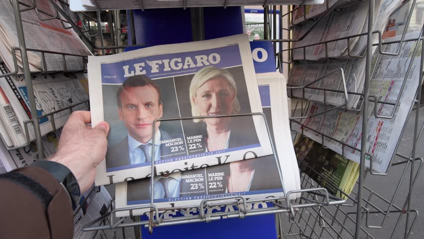 PARIS, FRANCE - APRIL 24, 2017: press kiosk at French newspaper Le Figaro with pictures of French Presidential election candidates, Emmanuel Macron, Marine Le Pen