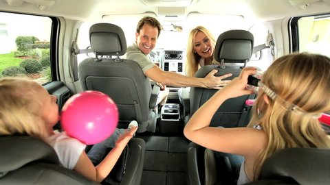 Happy Caucasian family in people carrier car ready for day beach
