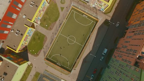 Above top view children play football soccer at school stadium aerial 4K UHD