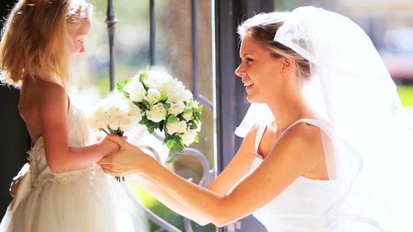 Beautiful young bride hugging cute little bridesmaid before wedding