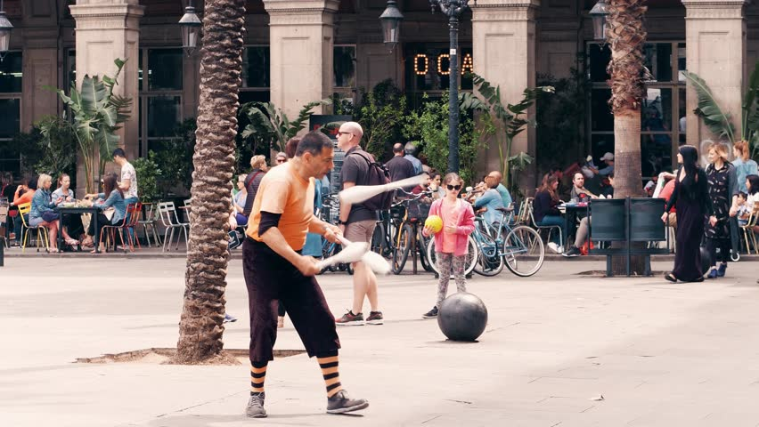 BARCELONA, SPAIN - APRIL, 16, 2017. Mature juggler performing in the street. 4K steadicam clip