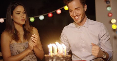 Young man blowing out the candles on his birthday cake watched by an excited laughing young woman with a string of party light decorations
