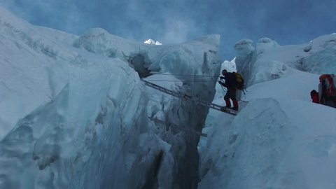 A mountaineer crossing a ladder over a glacier on route to the summit of Mount Everest. Nepalese Himalayas.