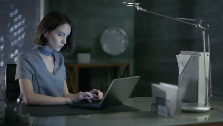 Stylish Female Top Manager Works on a Laptop in Her Private Office with Big City View. Her Workspace is Done in Dark Overtones, with Naked Cement Walls. Shot on RED EPIC-W 8K Helium Cinema Camera.