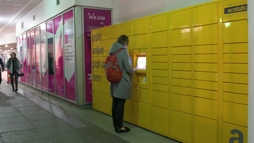 LONDON, UNITED KINGDOM - CIRCA 2017: Woman taking parcel from the Amazon locker orange delivery package locker in the University Campus - Amazon Locker self-service parcel delivery service