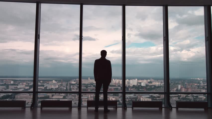 Rear view of man in formal suites who stand in front of panoramic window with city view. a man stands in front of big panoramic wiindow view from back. #26439365