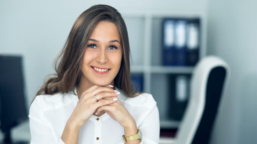 Cheerful businesswoman sitting at the table in office and looking at camera | Shutterstock HD Video #26445095