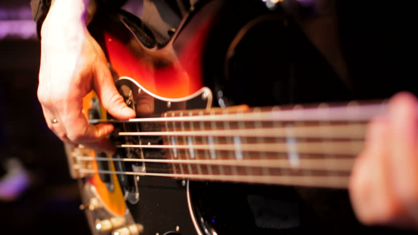 CloseUp of Bass Player Hands Playing Rock Music with Bass Guitar at the Concert in the Nightclub with Beautiful Light