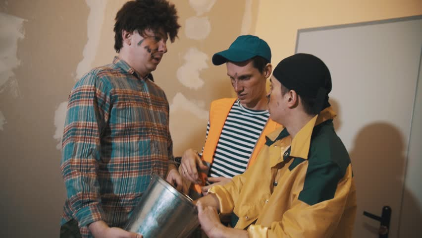 Three middle aged caucasian funny men dressed as dirty workers figuring out what inside tin bucket, laughing | Shutterstock HD Video #26463995