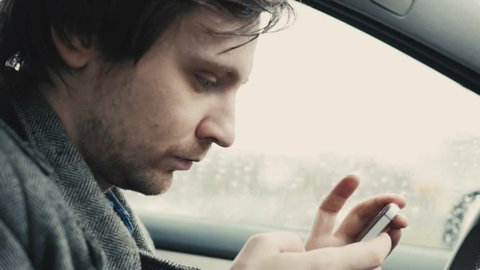 Hand using phone sending a text while driving, man voice control, safety use of phone
