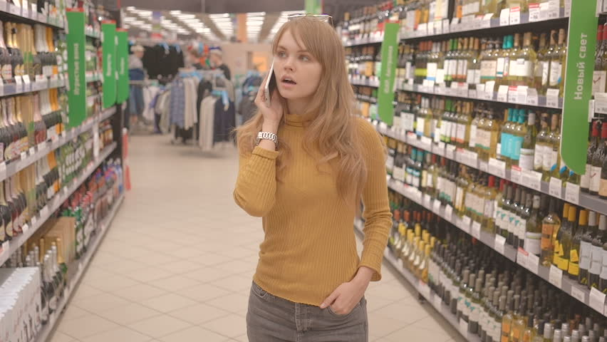 Woman with mobile talking and deciding what wine to buy in supermarket | Shutterstock HD Video #26483225