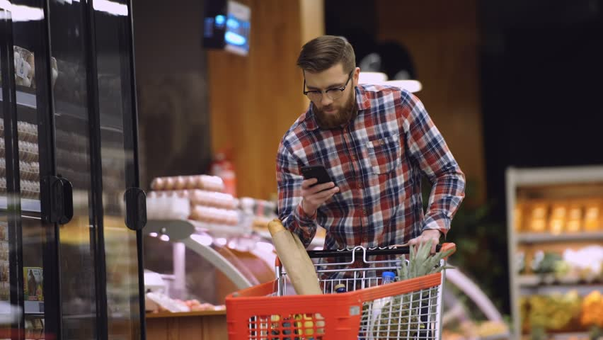 Bearded man in eyeglasses and shirt walking in supermarket with shopping trolley which looking on shopping list in the smartphone | Shutterstock HD Video #26494331