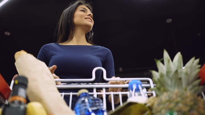 View from below of a happy funny woman walking in supermarket, pushing shopping trolley with convenience food and puts something in a trolley