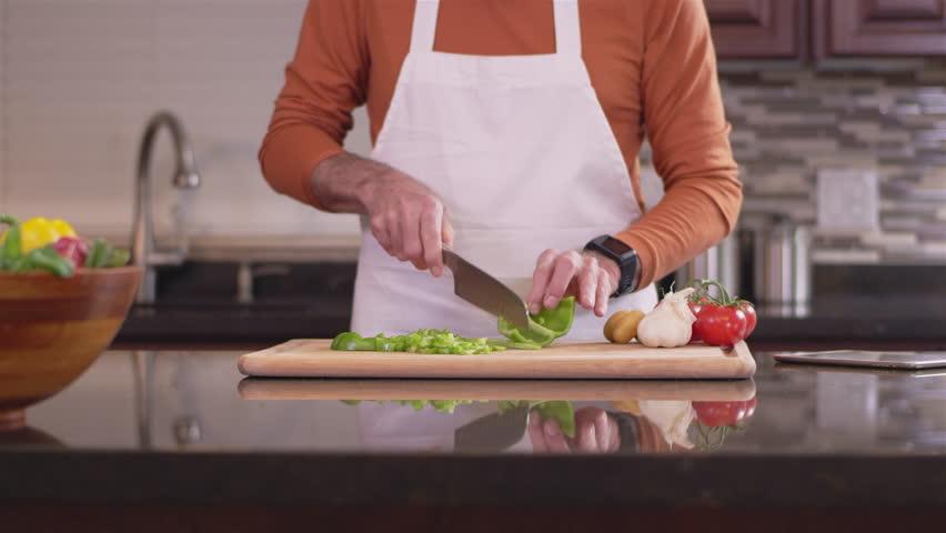Close up shot of an old chef chopping up a green bell pepper | Shutterstock HD Video #26505452