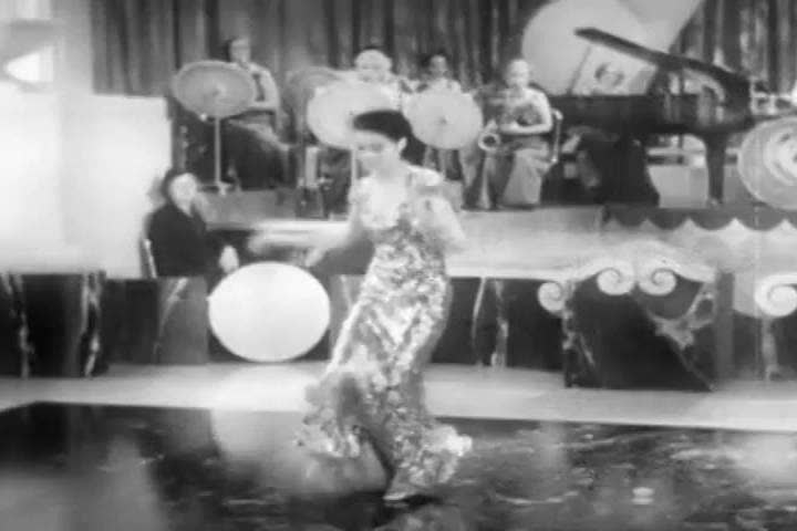 1940s: A well dressed elegant woman tap dances and sings in a ritzy nightclub in the 1940s.
