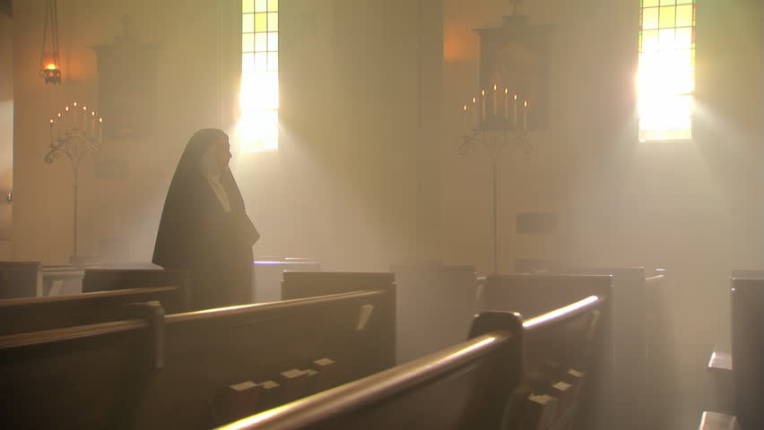 Nun walking slowly up aisle of Catholic church, votive candles in foreground