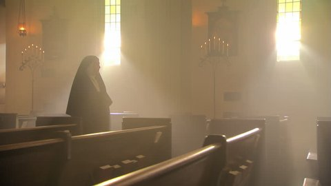 Nun walking slowly up aisle of Catholic church, votive candles in foreground