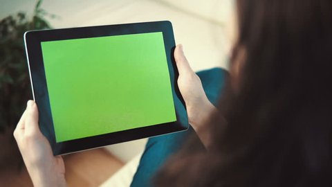 Indoor shot of a woman using tablet pc with green screen sitting on white sofa, pick and slide gestures, horizontal orientation