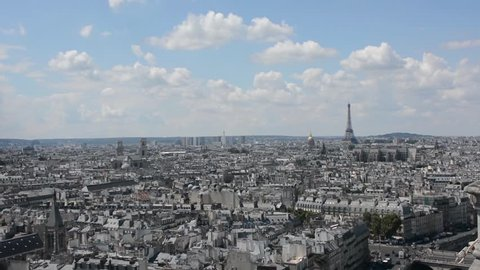 Paris. France. View of the Parisian rooftops and the panorama of Paris and the Eiffel Tower from the bell tower of Notre Dame. Cloudy sky bakground