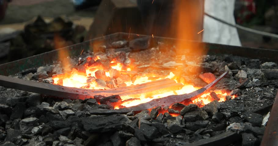 forge fire. sparks and flames from the fire being distributed in smithy - 4k stock video clip forge