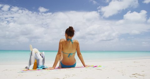 Beach woman sitting down on beach towel relaxing on beautiful caribbean beach.