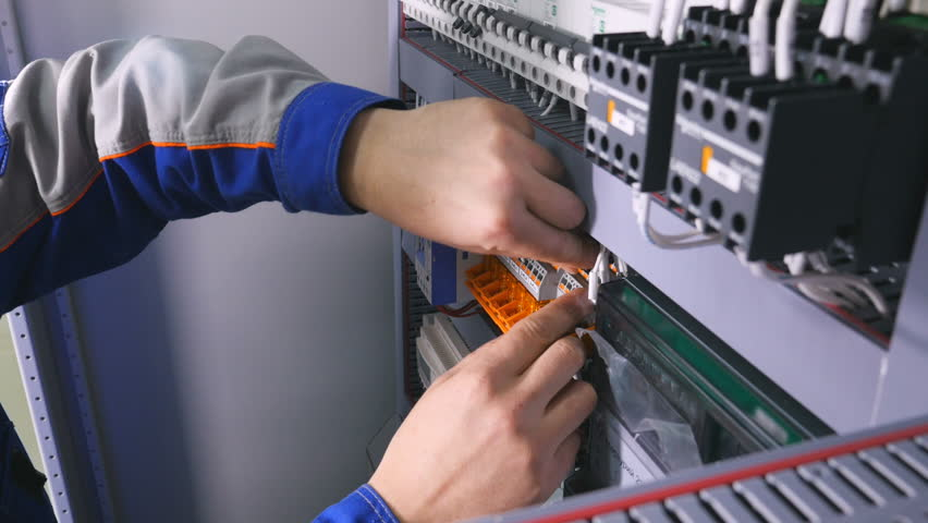 electrician installing wires, cables into a electricity power shield, fuse  box
